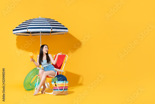 Fototapeta Surprised beautiful Asian woman sitting on beach chair