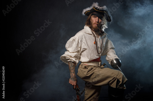 Portrait of pirate filibuster sea robber in suit with guns. Concept photo