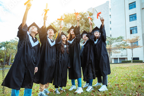 happy  students in graduation gowns holding diplomas on university campus Canvas Print