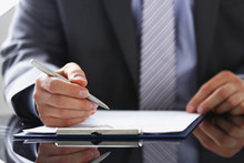 Male Arm In Suit And Tie Fill Form Clipped To Pad With Silver Pen Closeup. Sign Gesture Read Pact Sale Agent Bank Job Make Note Loan Credit Mortgage Investment Finance Chief Legal Law Concept