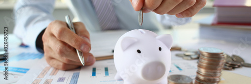 Cuadros en Lienzo Hand businessman putting pin money into pig