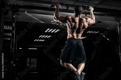 Fototapeta Muscular man bodybuilder training in gym and posing. Fit muscle guy workout with weights and barbell