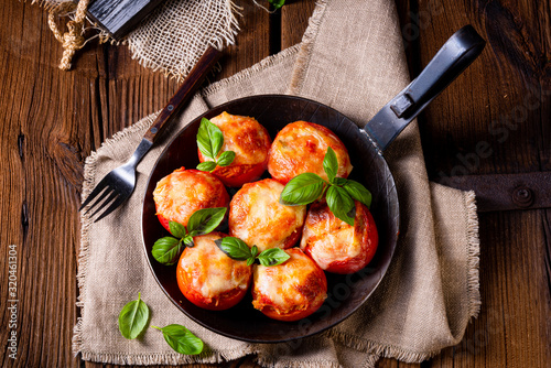 Fototapeta Stuffed tomatoes with minced meat and cheese obraz