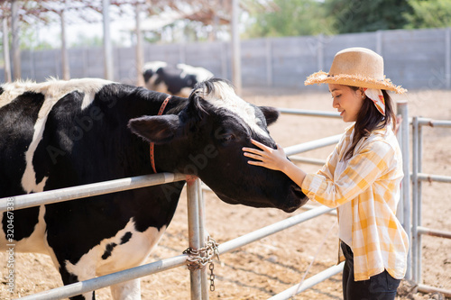 Fotografering Portrait asian owner of a cow farm standing on the farm she touches the cow's he