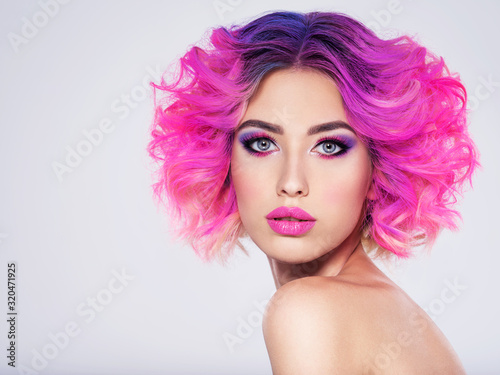 Obraz Portrait of beautiful young woman with bright pink makeup. Beautiful blonde with bright pink lipstick on her lips. Pretty girl with vivid hair. Blonde with brightly colored hair. Bright eye makeup. - fototapety do salonu