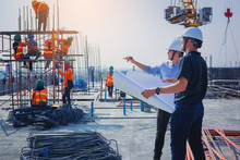 Structural Engineer And Architect Working With Blueprints Discuss At The Outdoors Construction Site.