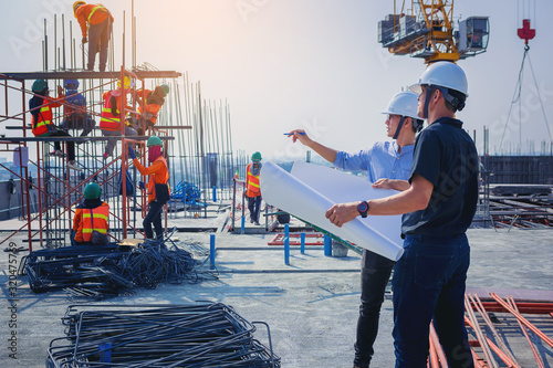 Structural engineer and architect working with blueprints discuss at the outdoors construction site Canvas Print