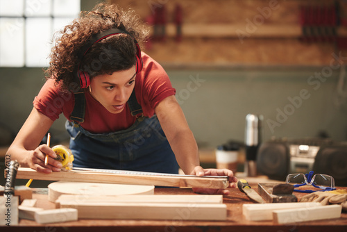 Photo Young concentrated curly woman in ear defenders and overall measuring wooden pla