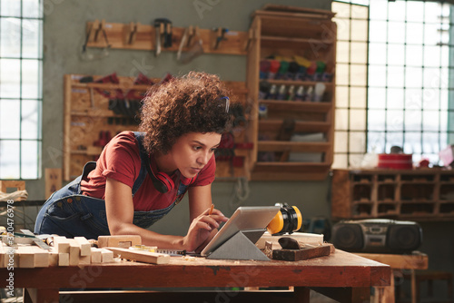 Photo Young concentrated woman with curly hair reading instructions on digital tablet