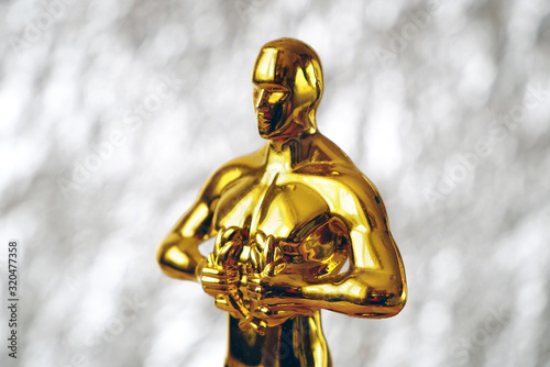 Hollywood  Golden Oscar Academy award statue on silver background. Success and victory concept. - 320477358