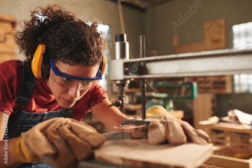 Obraz Close-up view of young concentrated female carpenter in safety glasses and ear defenders drilling hole in wooden plank with drill press - fototapety do salonu