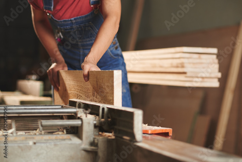 Fotomural Close-up view of unrecognizable carpenter in denim overall processing wooden boa