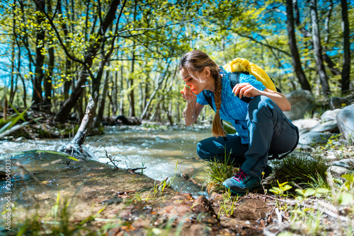 Woman refreshing herself with fresh water from creek while hiking Fotobehang