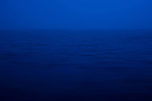 Natural Texture Of Deep Blue Calm Water In Dusk Close Up. Night Sea Of Blue Classic Color. Water Ripple Nature Background. Meditative Image Of Thick Fog Above Lake. Soft Light Shines On Water Surface.