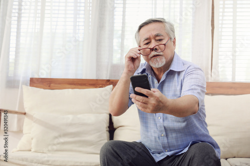 Fototapeta Older men move glasses down to look at the phone in the hand due to Hyperopia problems, which makes vision difficult.Health problems of the elderly. obraz