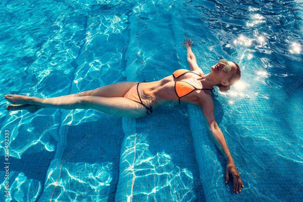 Fototapeta Beautiful woman relaxing in swimming pool of resort or hotel