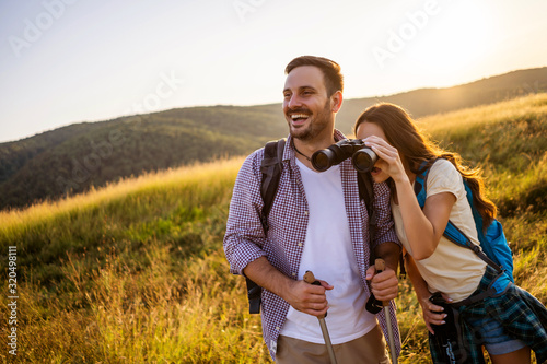Fototapeta Happy couple is hiking in mountain. They are watching nature with binoculars. obraz