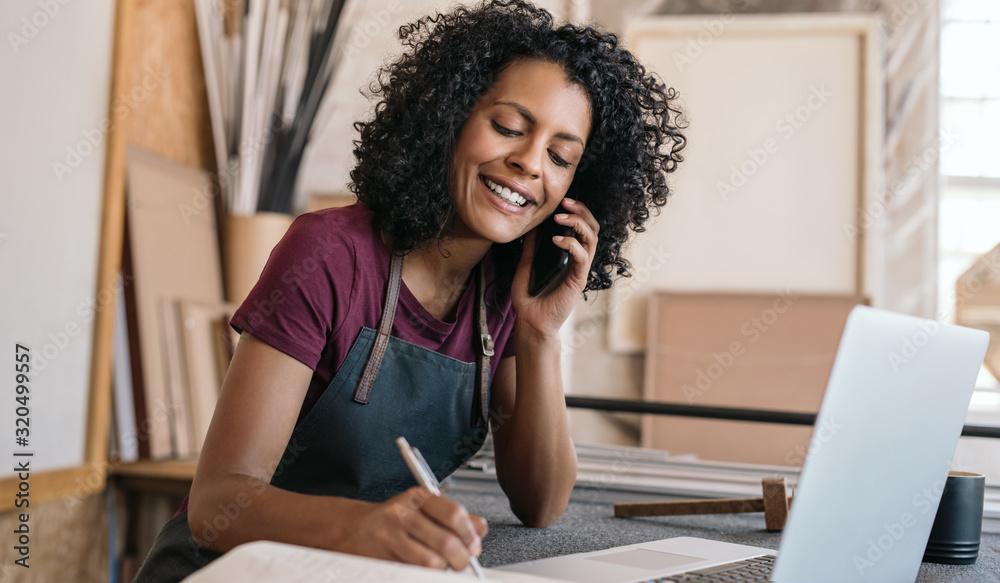 Fototapeta Smiling entrepreneur talking on the phone in her framing studio