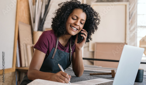 Smiling entrepreneur talking on the phone in her framing studio