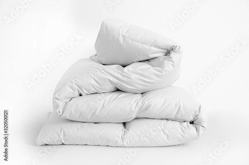 Photo Folded soft white duvet, blanket or bedspread, against white background