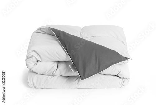 Folded soft white duvet, blanket or bedspread with the gray back side and empty white label, against white background Fototapete