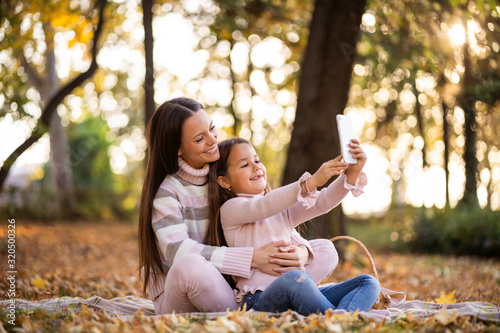 Obraz Mother and daughter using smartphone in autumn in park. - fototapety do salonu