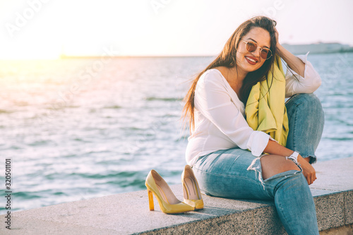 Happy plus size model taking off shoes and relaxing on city street Canvas Print