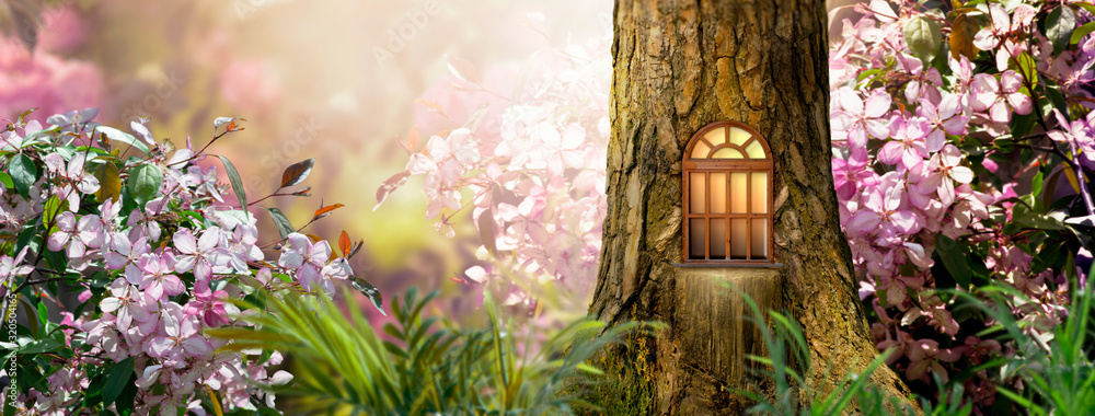 Fototapeta Enchanted fairy tale forest with magical shining window in hollow of fantasy pine tree elf house, blooming fabulous giant pink sakura cherry flower garden, building in wood in fairytale morning light