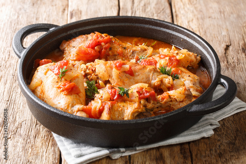 Fototapeta Tasty spicy rabbit stew in tomato sauce with white wine and herbs close-up in a pan. horizontal obraz