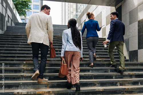 Photo Business people walking up the stairs when going to work in the morning, view fr