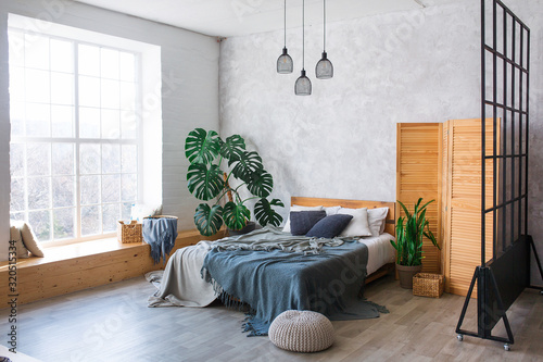 Obraz na plátně Cozy bedroom area at luxury studio apartment with a free layout in a loft style with big panoramic window and green plant