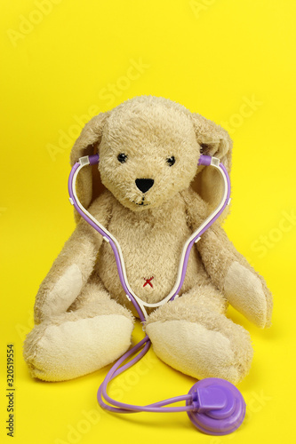 hare toy doctor in a stethoscope or phonendoscope on a yellow background