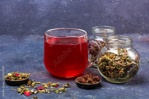 Fototapeta Red tea (rooibos, hibiscus, karkade) in glass cup and jars of dry tea leaf and petals on dark background. Herbal, vitamin, detox tea for cold and flu. Close up, copy space for text obraz