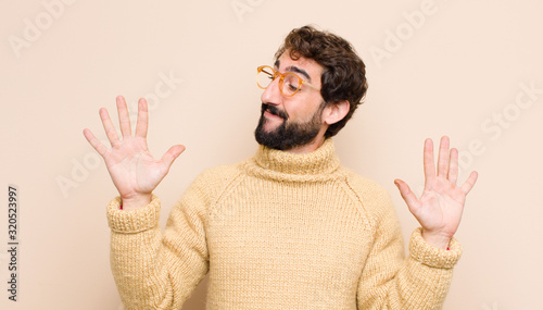 young cool man smiling and looking friendly, showing number ten or tenth with ha Wallpaper Mural