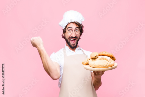 Fotografie, Obraz young crazy baker man holding bread against pink wall