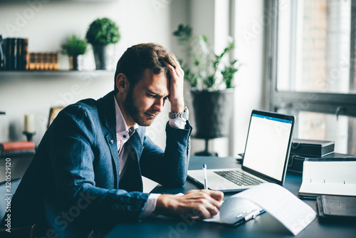 Fototapety, obrazy: Manager sitting at the desk with laptop, reading important documents with puzzled expression and holding head with his hand.