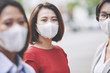 Leinwanddruck Bild - Portrait of beautiful young Vietnamese woman in medical mask standing on the street of her polluted or infected city