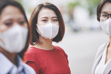 Portrait Of Beautiful Young Vietnamese Woman In Medical Mask Standing On The Street Of Her Polluted Or Infected City