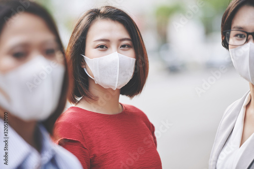 obraz PCV Portrait of beautiful young Vietnamese woman in medical mask standing on the street of her polluted or infected city