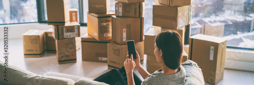 Moving boxes woman using phone panoramic for move to college leaving apartment ready for movers pick-up with packages of cardboard box for new home move in. Banner. - 320533332
