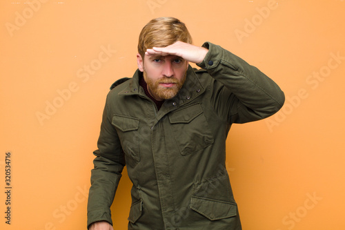 young blonde man looking bewildered and astonished, with hand over forehead look Wallpaper Mural