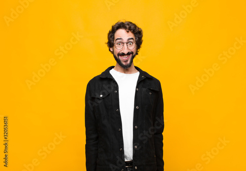 Photo young crazy handsome man looking happy and goofy with a broad, fun, loony smile