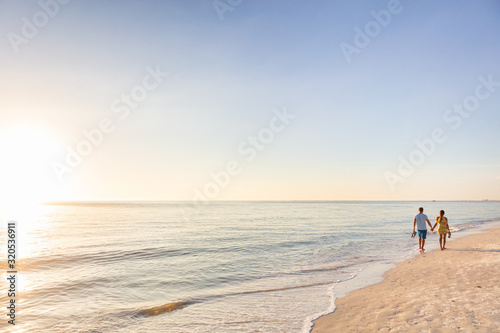 Leinwand Poster Beach relaxing vacation - travel tourists couple walking on beach at sunset landscape background