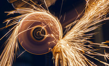 A Man Cuts Metal Using An Angle Grinder Close-up. Many Sparks