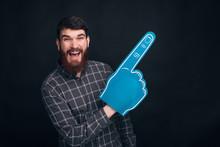 I Am Number One Fan. Screaming Of Joy Bearded Man Is Wearing A Fan Foam Glove, Pointing Aside On Black Background.