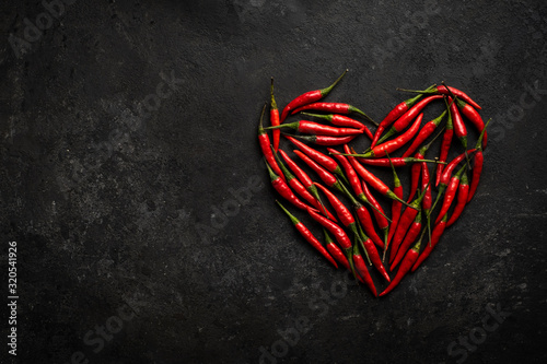 Spicy red chili pepper in the shape of a heart on a dark stone background, desig Wallpaper Mural