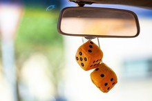 Fuzzy Dice Haning From Rear View Mirror Of Classic Car