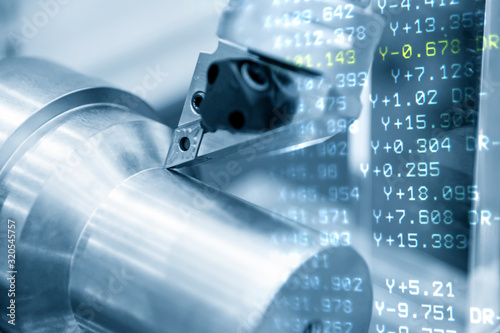 The abstract scene of CNC lathe machine and the G-code data background while cutting the the metal shaft parts. The automotive parts production processing by CNC turning machine .