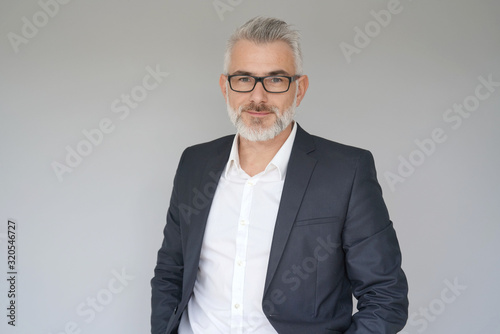 Portrait of businessman standing on grey background - 320546727