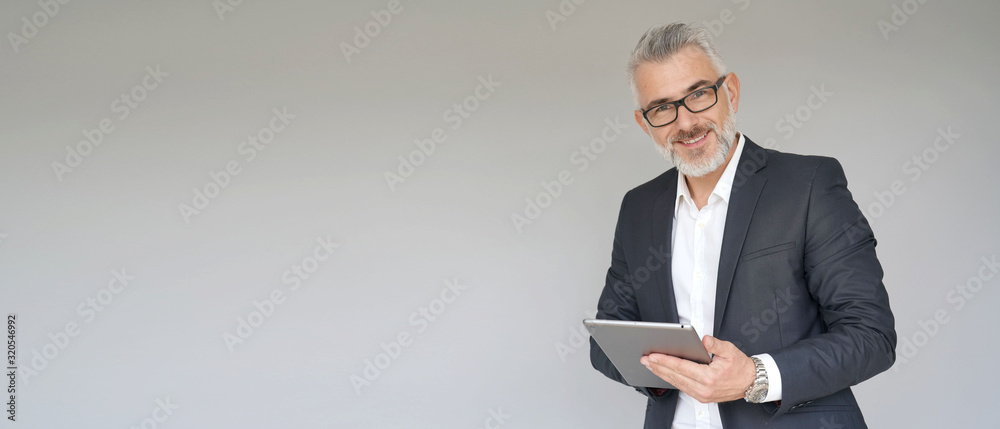 Fototapeta Businessman using digital tablet isolated on background- template